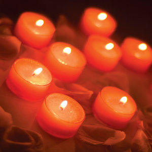Lighting candles as part of a funeral ritual or ceremony.